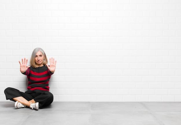 Senior of middelbare leeftijd mooie vrouw op zoek ernstig, ongelukkig, boos en ontstemd toegang te verbieden of stop te zeggen met beide open handpalmen