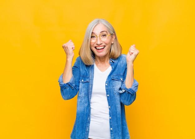 Senior of middelbare leeftijd mooie vrouw voelen geschokt, opgewonden en gelukkig, lachen en vieren van succes, zeg wow!