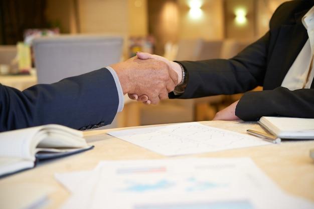 Senior ondernemers handen schudden na het bespreken van rapporten