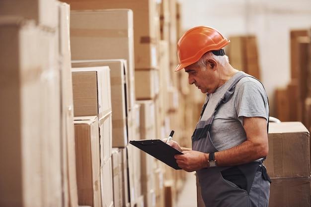 Senior opslagmedewerker in uniform en notitieblok in handen controleert de productie.
