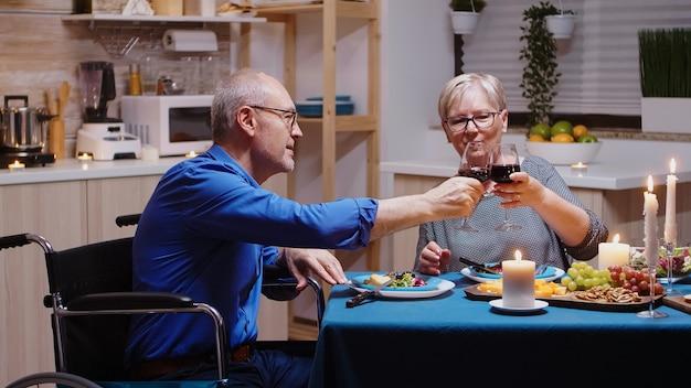Senior oude man in rolstoel dineren met zijn vrolijke vrouw aan de tafel in de keuken. geïmobiliseerde verlamde gehandicapte bejaarde echtgenoot die romantisch diner heeft