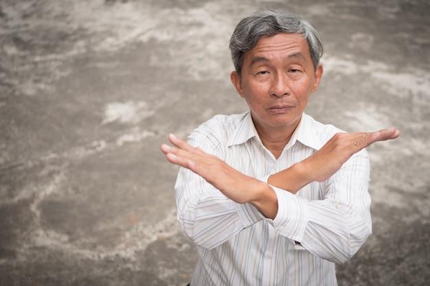 Senior oude man kruising arm zegt nee, gebaar afwijzen
