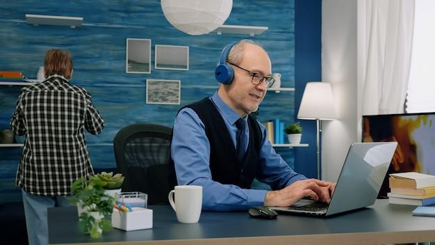 Senior oude man luistert muziek op koptelefoon terwijl hij op laptop werkt
