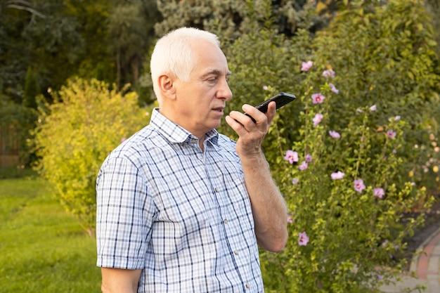 Senior oude man met behulp van mobiele telefoon met gesproken zoekopdrachten in groen park, moderne technologieën