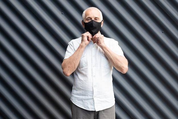 Senior oude man met een beschermend medisch masker aanraken van zijn gezicht, plaats voor tekst, copyspace
