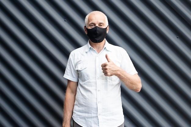 Senior oude man met een beschermend medisch masker duimen opdagen