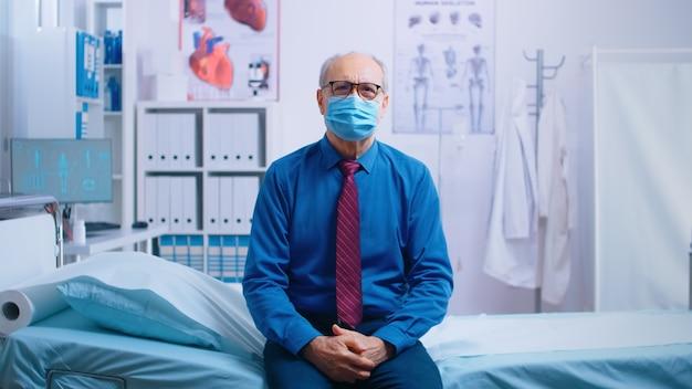 Senior oude man wacht op doktersresultaten, zit op de rand van het ziekenhuisbed, maakt zich zorgen en draagt een masker. covid-19 medische zorgoverleg, wereldwijde pandemie. privé moderne gezondheidskliniek