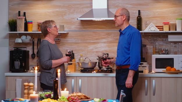 Senior oude paar wijn drinken en praten, zittend in de buurt van keukentafel. man en vrouw bespreken grappige dingen na een romantisch diner, vieren hun jubileum in de eetkamer.