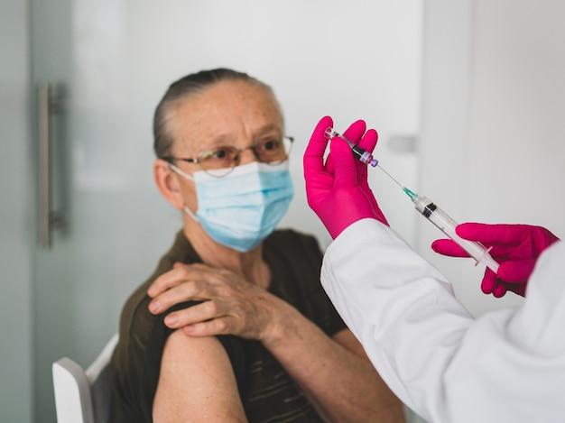 Senior oude vrouw in het ziekenhuis vaccin krijgen