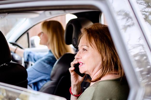 Senior oude vrouw met behulp van mobiele telefoon zitten op de achterbank van de auto tijdens road trip. dochter rijden oude dame