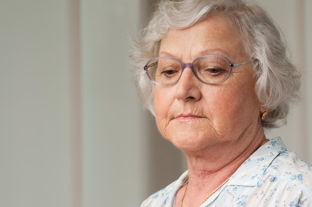 Senior oude vrouw neerkijkt met verdriet, indoor close-up shot