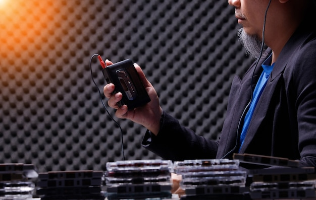 Senior oudere man houdt vintage cassettespeler en bedrade hoofdtelefoon vast in geluiddichte kamer en voorgrond met veel cassettebandjes. kopieer ruimte