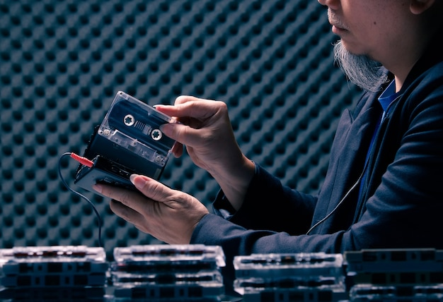 Senior oudere man zet vintage cassettebandje in speler en bedrade hoofdtelefoon in geluiddichte kamer en voorgrond met veel cassettebandjes. kopieer ruimte