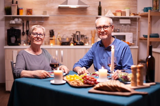 Senior paar camera kijken tijdens relatieviering met feestelijk diner in de keuken. verjaardag, vrije tijd, gepensioneerd, familie, romantisch
