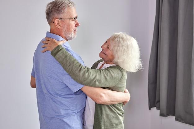 Senior paar dansen in de woonkamer, man met de hand van volwassen vrouw samen genieten van plezier, vakantie, vrije tijd pensioen ifestyle thuis doorbrengen. in vrijetijdskleding