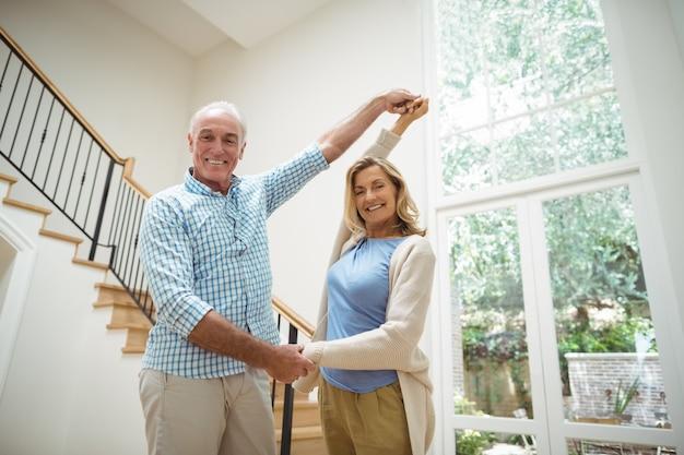 Senior paar dansen samen in de woonkamer