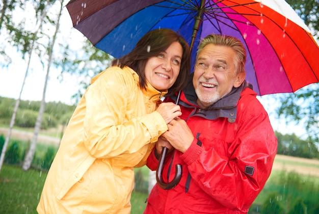 Senior paar delen een paraplu in de regen