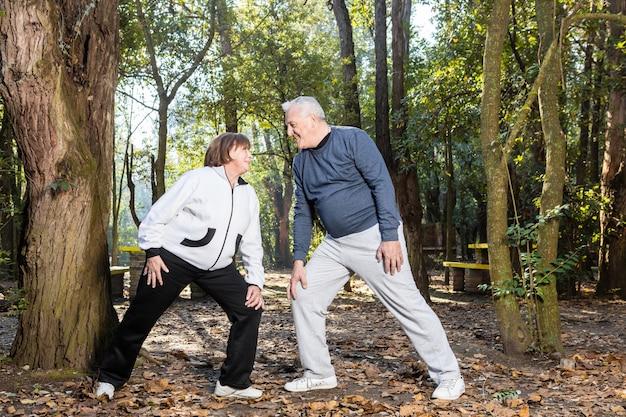 Senior paar doen warming-up oefeningen samen