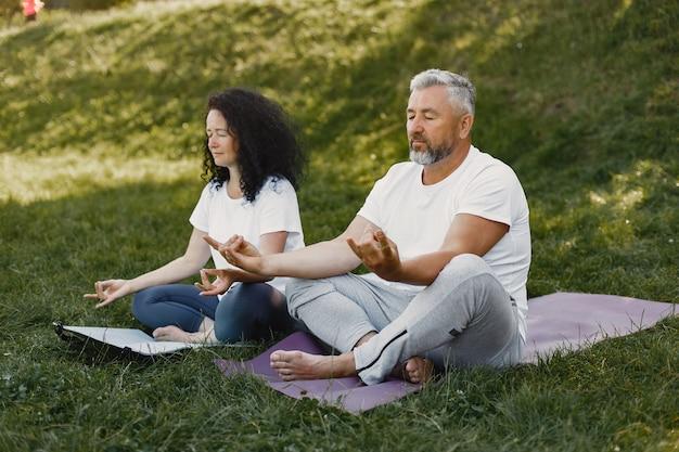 Senior paar doet yoga buitenshuis. die zich uitstrekt in het park tijdens zonsopgang. brunette in een wit t-shirt.