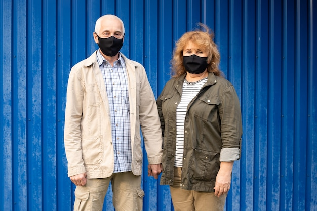 Senior paar dragen masker om te beschermen tegen virussen op blauw