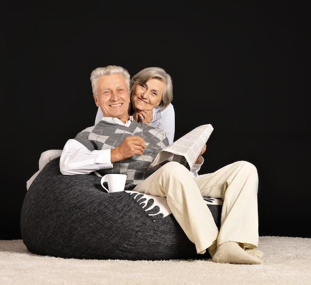 Senior paar drinken thee zittend in zwarte fauteuil