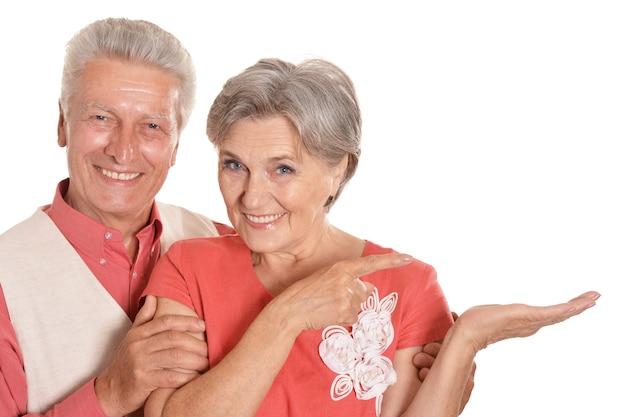 Senior paar geïsoleerd op een witte achtergrond wijzend op iets