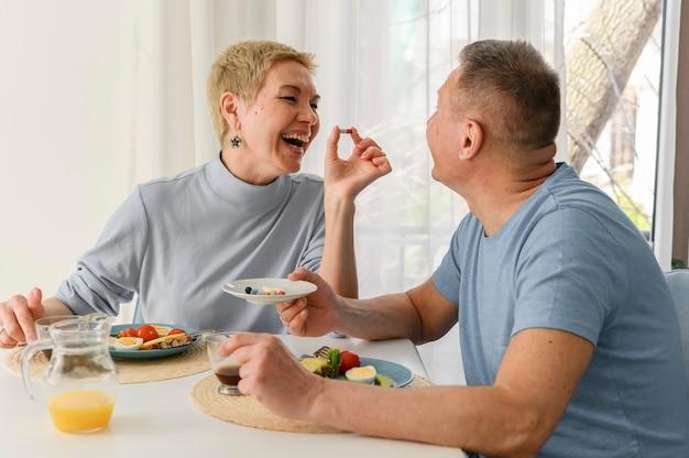 Senior paar geniet van het eten van gezond ontbijt samen portret van gelukkige paar