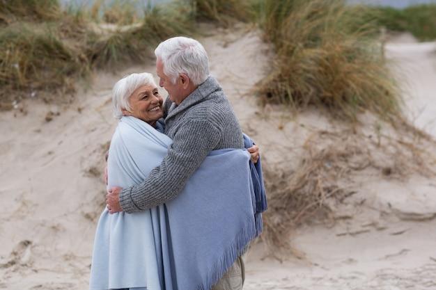 Senior paar gewikkeld in sjaal op het strand