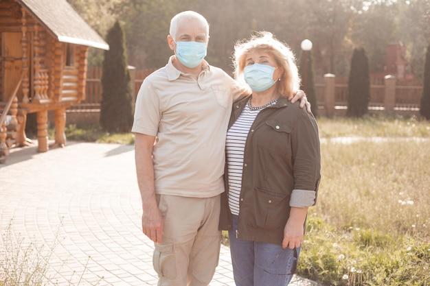 Senior paar in maskers in de natuur, coronavirus quarantaine