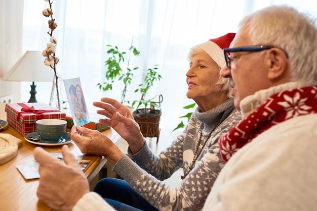 Senior paar kijken naar foto's op kerstmis