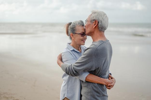Senior paar knuffelen en kussen elk op het strand. plan levensverzekeringen met een gelukkig pensioenconcept.