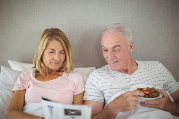 Senior paar krant lezen tijdens het ontbijt