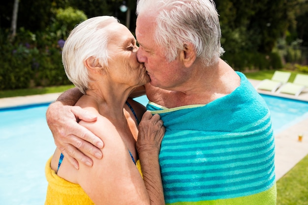 Senior paar kussen elkaar bij het zwembad op een zonnige dag