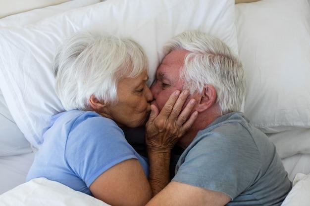 Senior paar kussen elkaar in de slaapkamer thuis