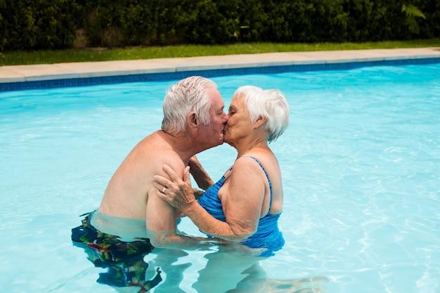Senior paar kussen elkaar in het zwembad op een zonnige dag
