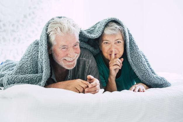 Senior paar liggend op de voorkant en gebaren vinger op de lippen op bed. bejaard echtpaar dat vrije tijd met elkaar doorbrengt. gelukkig oud paar liggend op een gezellig bed bedekt met deken met vinger op lippen