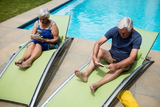 Senior paar met behulp van digitale tablet op lounge stoel bij zwembad