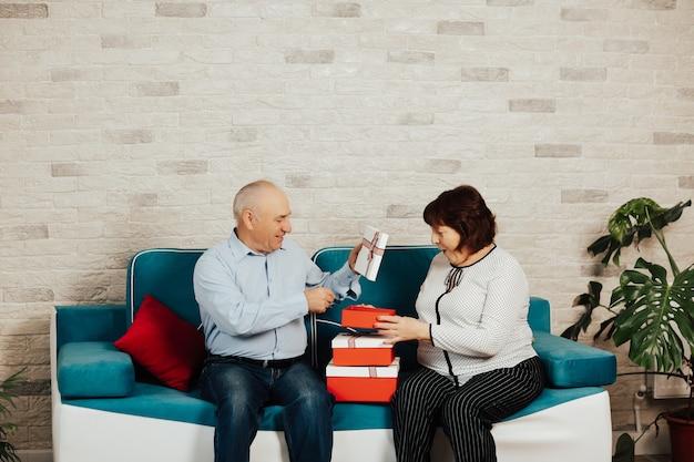 Senior paar met rood-witte geschenkdozen zittend op de bank thuis.