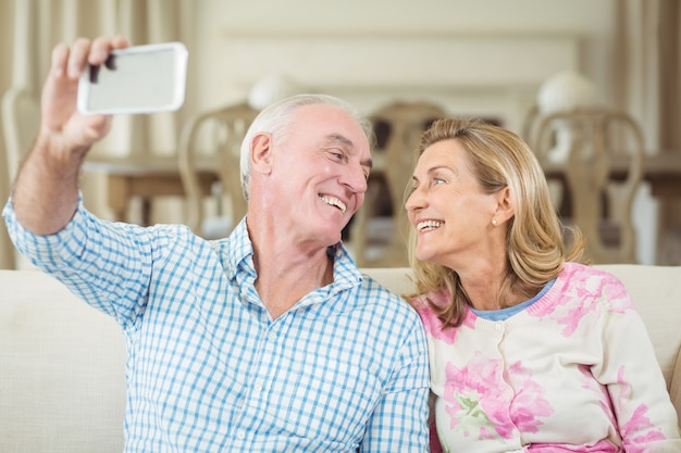 Senior paar nemen een selfie op mobiele telefoon in de woonkamer