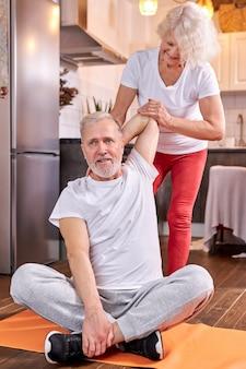 Senior paar oefenen thuis, vrouw helpen man uit te rekken, zittend op de vloer. welzijn, gezonde levensstijl concept