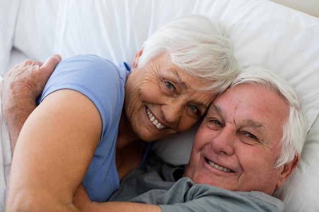 Senior paar omhelzen elkaar in de slaapkamer thuis