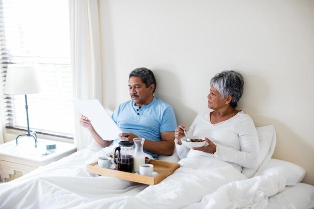 Senior paar ontbijten in de slaapkamer