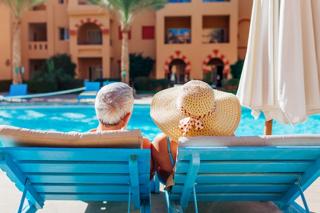 Senior paar ontspannen bij het zwembad. mensen die van vakantie genieten. valentijnsdag