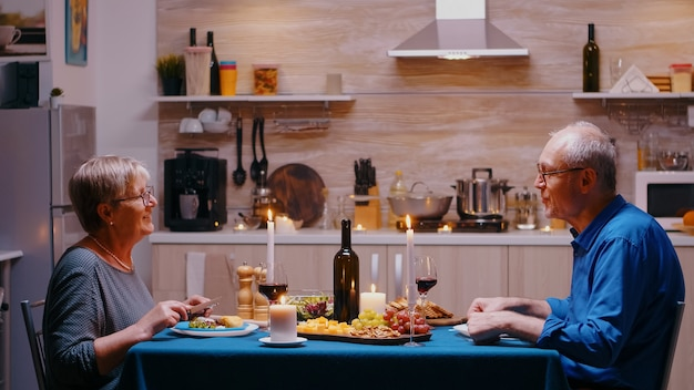 Senior paar ontspannen dineren en samen wijnglazen drinken in de keuken thuis met een romantisch diner. gepensioneerd paar dat hun verjaardag viert in de eetkamer.