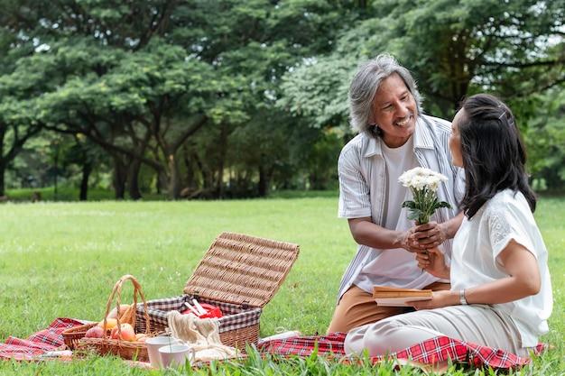 Senior paar ontspannen en picknick in het park. vrouw geeft bloem aan mijn man.