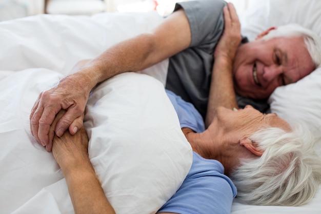 Senior paar ontspannen in de slaapkamer thuis