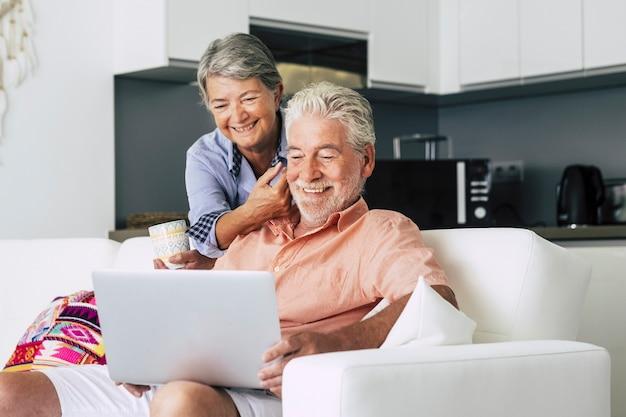 Senior paar ontspannen samen in de keuken met een laptop en met een kopje koffie of thee