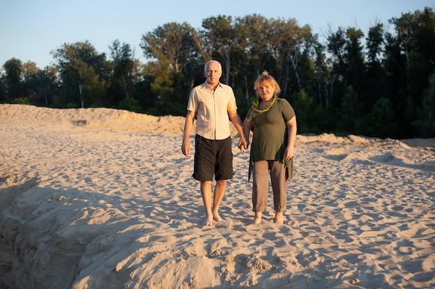 Senior paar op een wandeling in de zomer strand