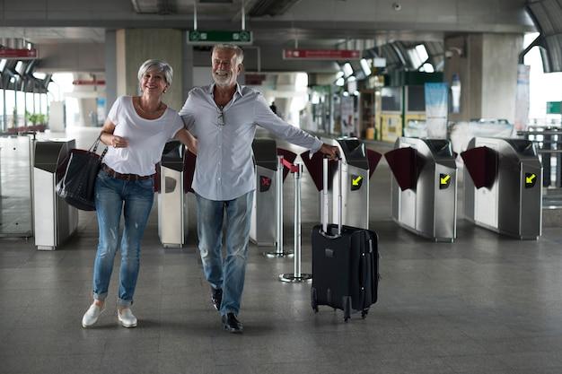 Senior paar reizen trein ticket poort