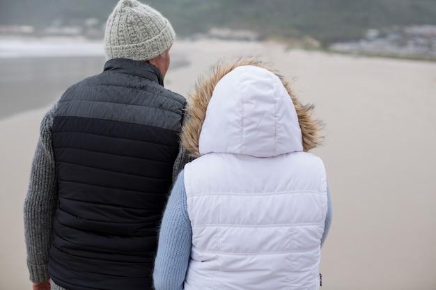 Senior paar samen wandelen op het strand